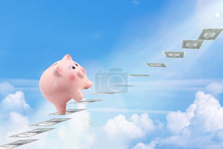 Photo for Pretty Piggy Bank Climbing Stairs for Success Made of Dollar Banknotes Above the Clouds - Royalty Free Image