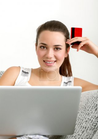 Photo pour Shopping en ligne - Belle jeune femme assise sur le canapé th avec carte Cradit - image libre de droit