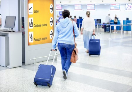 Photo for Passengers at the Airport go with Suitcase and Leather Bag - Royalty Free Image