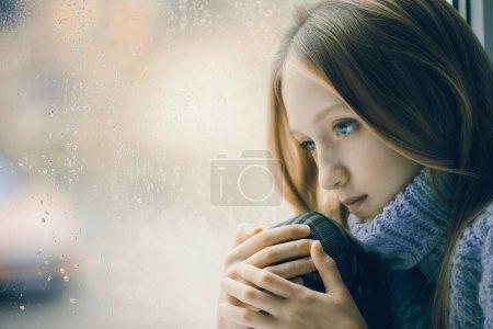 Photo pour Portrait d'une adolescente triste avec de longs cheveux blonds. Elle est assise sur une fenêtre sous la pluie - image libre de droit