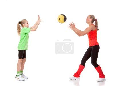 Photo pour Tir plein de corps d'une petite fille faisant l'exercice avec un instructeur - image libre de droit