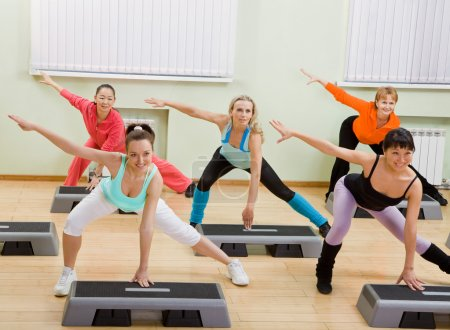 Women of Different Age Doing Step Aerobics in the Gym