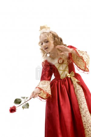 Beautiful little princess using red rose like a magic wand