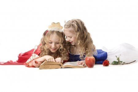 Two happy little princesses reading a magic book
