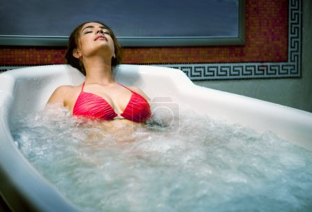 Photo for Healthy Spa: Young Beautiful Relaxing Woman Lying in the Bath with Hydro Massage. - Royalty Free Image
