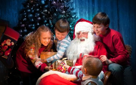 Photo for Group portrait of Kind Santa Claus sitting with Happy Children. - Royalty Free Image