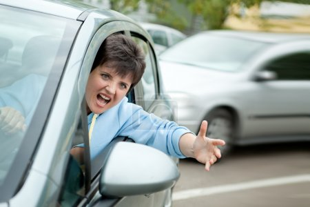 Photo for Young Woman Driver Yelling and Shaking her Wrist out Car Window. - Royalty Free Image