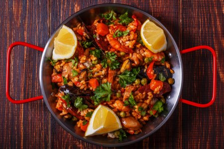 Paella with chicken, chorizo, seafood, vegetables and saffron.