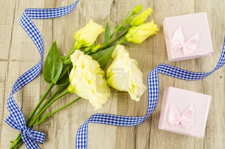 Yellow flower and gift box on wooden background