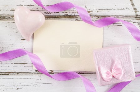 Empty card with gift box and heart on wooden table