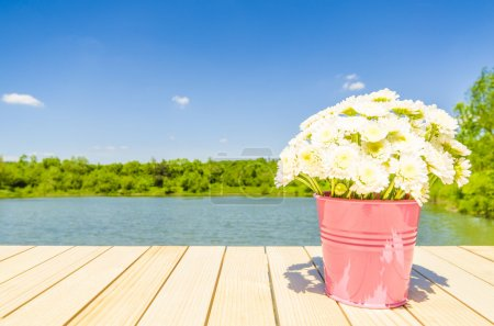 Bucket full of flowers on wooden table with landscape