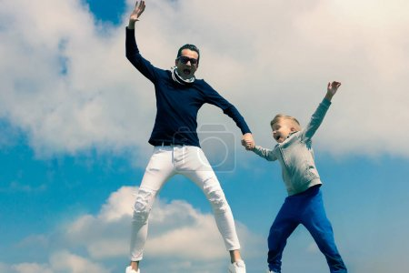 Photo for Carefree father and son having fun and jumping with arms raised against the sky. Copy space. - Royalty Free Image