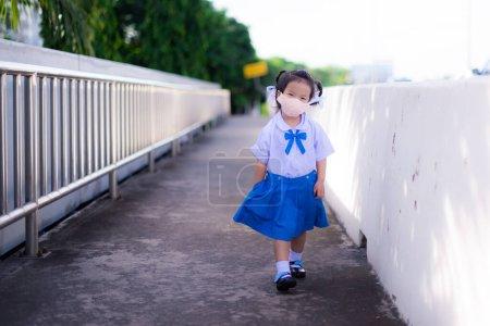 Une écolière asiatique portant l'uniforme de l'école marchait joyeusement vers l'école. Enfant portant un masque en tissu orange. Doux sourire sous masque. Le gamin a mis sa main dans la poche de sa jupe. Fille a 3 ans.
