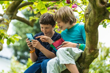 Photo for Two boys sitting on tree in garden and playing pocket games - Royalty Free Image