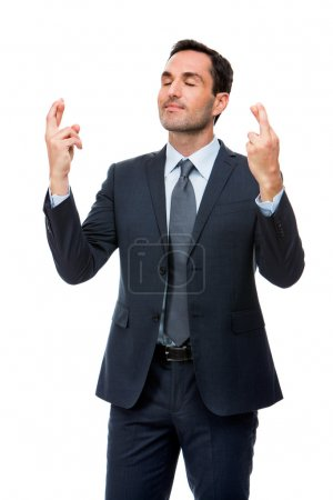 Half length portrait of a businessman with eyes closed and fingers crossed