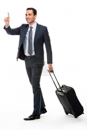 Full length portrait of a businessman with trolley stopping a taxi