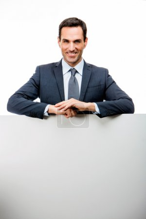 Half length portrait of a smiling businessman leaning on a white placard