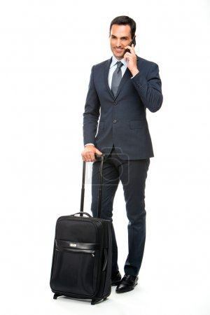 Full length portrait of a smiling businessman with trolley talking on the phone