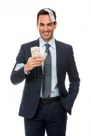 Half lenth portrait of a businessman smiling in falling money