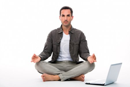 Man sitted on the floor looking at the camera and practicing yoga with laptop next to him