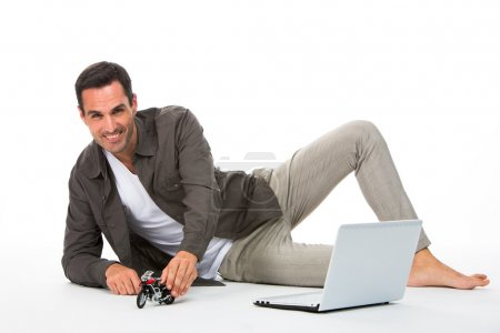 Man laying on the floor, smiling at camera playing with a motorbike scale model and laptop next to him
