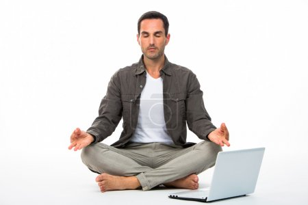 Man sitted on the floor with eyes closed practicing yoga with laptop next to him