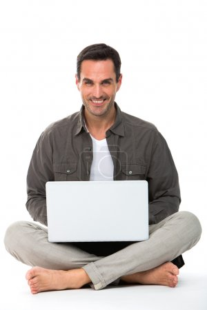 Man sitted on the floor, smiling at camera and working with his laptop