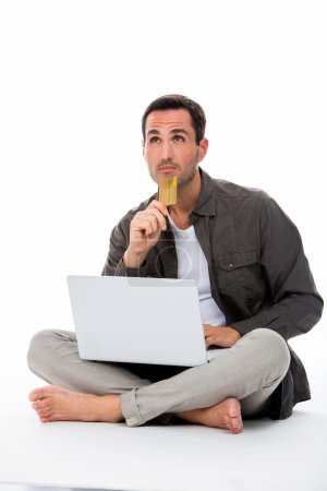 Thoughtful man sitted on the floor holding credit card and buying online