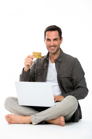Man sitted on the floor, smiling at camera, showing credit card and buying online