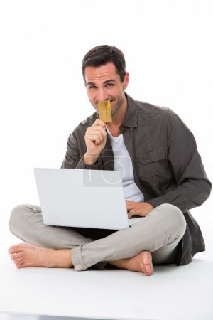 Man sitted on the floor, smiling at camera, holding credit card and buying online
