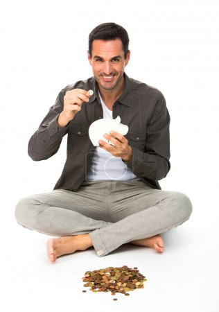 Man sitted on the floor, smiling at camera, holding a coin to be placed in a piggybank