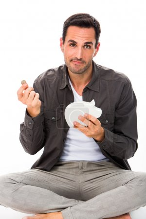 Man sitted on the floor, looking at camera, putting a coin in a piggybank