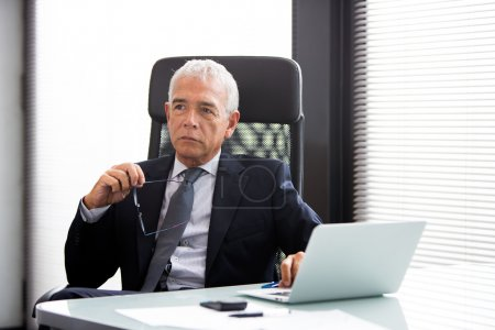 Half length portrait of a thoughtful businessman in the office with laptop computer and holding glasses