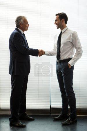 Full length portrait of two businessmen standing up, smiling and shaking hands