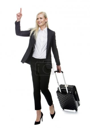 Blonde businesswoman with suitcase smiling and stopping a taxi