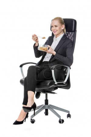 Blonde businesswoman on a chair and having lunch