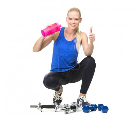 Blonde woman drinking after exercising with weights