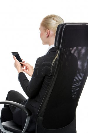 Businesswoman seated on a chair with mobile phone