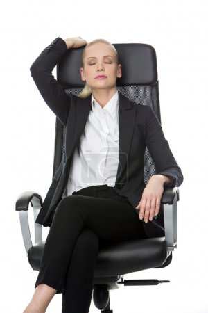 Businesswoman relaxing on a chair with eyes closed