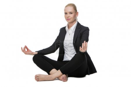 Businesswoman seated on the floor doing a yoga position