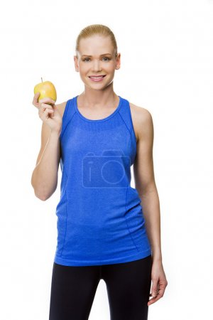 Woman in fitness clothing with apple