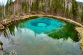 Geyser lake with clear cyan water