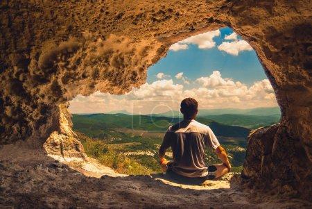Photo pour L'homme qui médite dans une grotte surplombant la vallée de montagne - image libre de droit