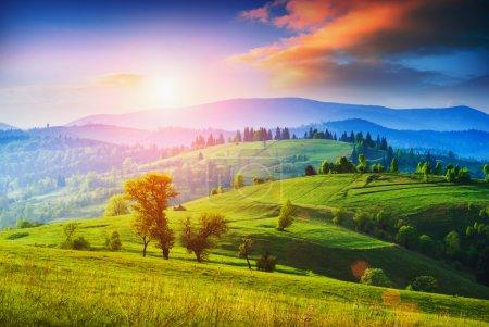 Photo pour Tôt le matin dans une vallée des Carpates avec prairie verte et nuages colorés dans une belle lumière du lever du soleil - image libre de droit
