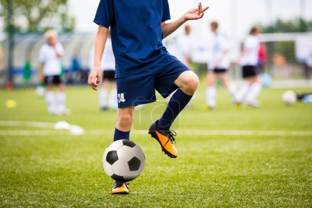 Boy Playing Soccer Football Match on a Sports Stadium