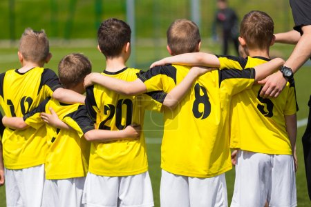 Young sport team with coach on sports field. Football; soccer; hockey teamwork
