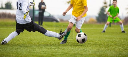 Young soccer goalkeeper save and running forward