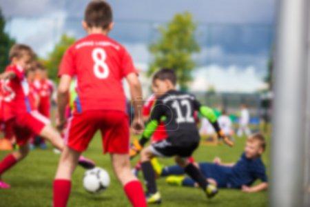 Blurred sport soccer football background. Young boys playing football match. children's soccer match. Red against black team.