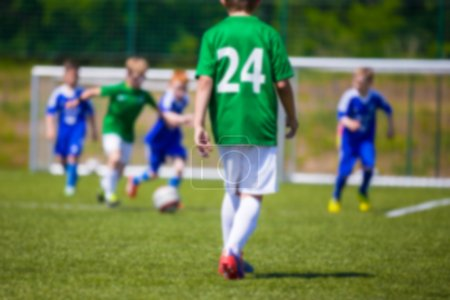 Blurred sport soccer football background. Young boys playing football match. Blue against green team.