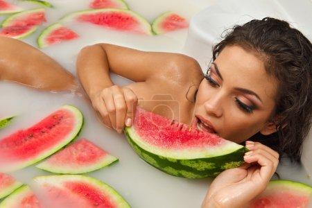 Photo pour Jolie fille nue apprécier le bain avec du lait et de la pastèque - image libre de droit